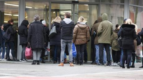 Menschen warten vor der Öffnung einer Aldi-Filiale vor dem Eingang.