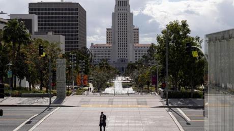 Ein Fußgänger überquert Grand Avenue in Los Angeles. Nun ist in Kalifornien eine Ausgangssperre für die gesamte Bevölkerung verhängt worden.