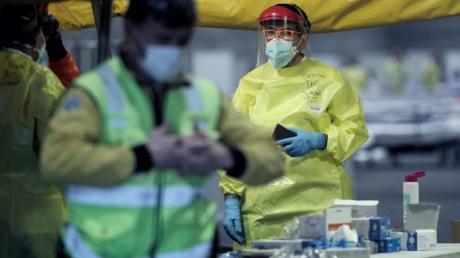 Gesundheitspersonal mit Schutzkleidung auf dem Gelände der Madrider Messe, wo Patienten mit leichten Symptomen behandelt werden.