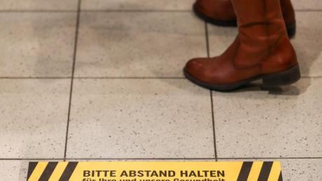 Eine Frau steht an der Kasse eines Supermarkt hinter einem Warnaufkleber, der um Abstand bitte.
