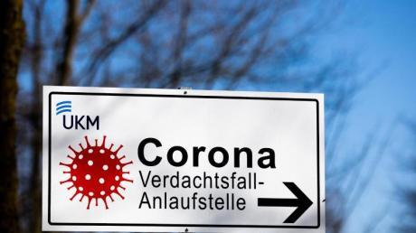 Ein Hinweisschild mit der Aufschrift «Corona Verdachtsfall-Anlaufstelle» steht vor der Uniklinik Münster.