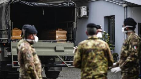 Italienische Soldaten mit Mundschutz vor einem Militärfahrzeug mit Särgen vonCorona-Opfern.
