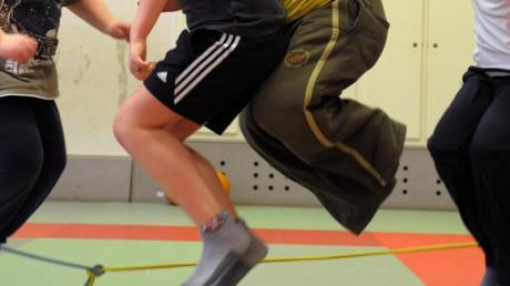 In einer Sporthalle nehmen übergewichtige Kinder an einem Sportprogramm teil.