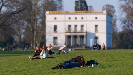 Menschen genießen das sonnige Wetter auf einer Wiese vor dem Jenisch-Haus in Hamburg.