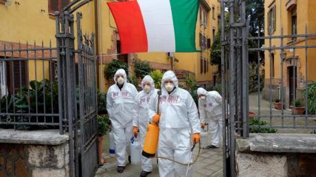 Arbeiter in Schutzkleidung desinfizieren die Gehwege eines Viertels in Rom.