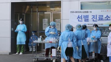 Medizinisches Personal in Schutzausrüstung steht vor einem Krankenhaus in Südkorea.