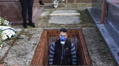 Ein Leichenbestatter in Spanien bereitet ein Grab vor während der Beerdigung einer 86-jährigen Frau mitten in der Corona-Krise.