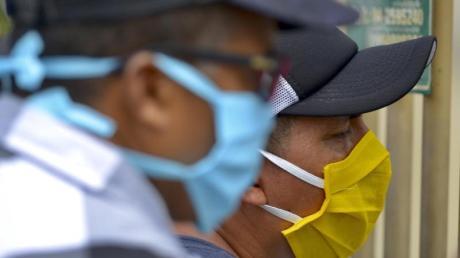 Männer mit Mundschutzmasken am Eingang des Friedhofs «Jardines de la Esperanza» in der Hafenstadt Guayaquil in Ecuador.