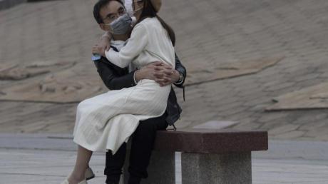 Ein Paar mit Mundschutz sitzt auf einer Bank im chinesischen Wuhan. In der Stadt, in der die Corona-Pandemie begann, fallen nach elf Wochen die letzten Bewegungsbeschränkungen für die elf Millionen Bewohner.