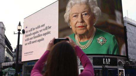 Ein Bild von Königin Elizabeth II. und Zitate aus ihrer Ansprache auf Anzeigetafeln am Piccadilly Circus in London.