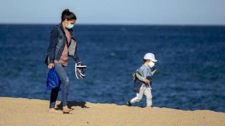 Eine Frau und ihr Sohn an einem Strand in der Nähe von Barcelona in Spanien.