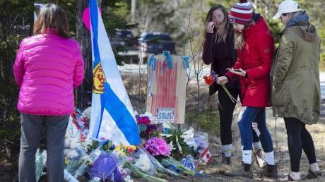 Frauen legen Blumen an einer Gedenkstätte für die Opfer des Amoklaufs in Nova Scotia ab. Als Reaktion auf die schlimme Bluttat hat Kanada die Waffengesetze verschärft.