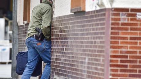 Ein Polizeibeamter betritt ein Haus in Bonn. Laut Staatsanwaltschaft konnten die Beamten mutmaßliche Beweismittel sicherstellen.