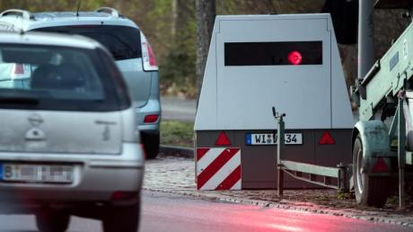 Ein Auto fährt an einem mobilen Blitzwagen, einem Geschwindigkeitsmessanhänger der Marke Votronic, vorbei.