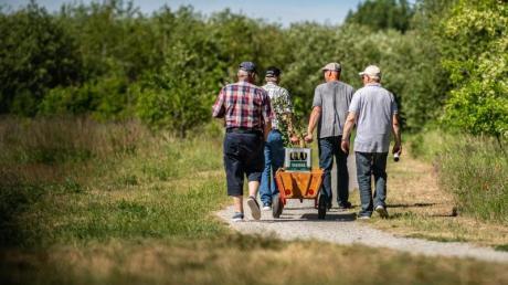 Traditionalisten: Vier Männer gehen am Vatertag mit einem Bollerwagen, auf dem zwei Kisten Bier stehen, an der Ems in Warendorf entlang.
