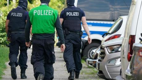 Bundespolizisten laufen vor einem Haus in Leipzig Grünau entlang.