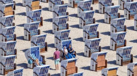 Erste Urlauber sitzen in Strandkörben am Ostseestrand in Warnemünde.