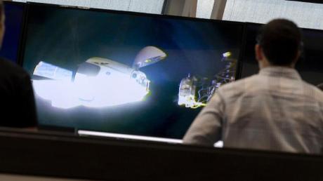 Mitarbeiter verfolgen auf Bildschirmen im Weltraumbahnhof des Kennedy Space Centers in Cape Canaveral, wie sich die Raumkapsel der «Crew Dragon» der ISS zum Andocken nähert.