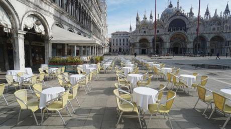 Leere Stühle und Tische vor einem Restaurant auf dem Markusplatz.