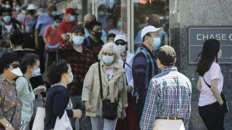 Menschen mit Masken warten im New Yorker Stadtbezirk Queens vor dem Eingang einer Bank.