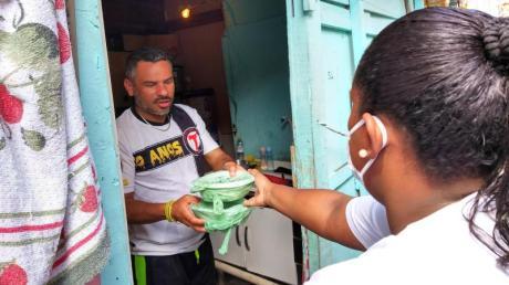 """Laryssa da Silva reicht einem Mann zwei Essenspakete in die Wohnung. Sie ist eine von 700 """"Straßenpräsidenten"""" in Paraisopolis."""