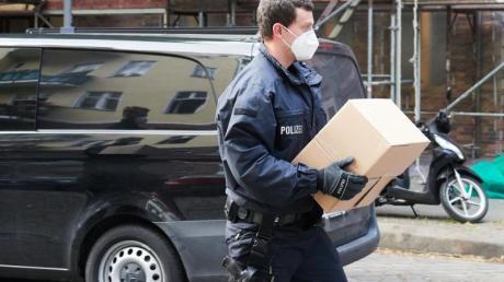 Ein Polizist trägt sichergestelltes Beweismaterial zu einem Auto.