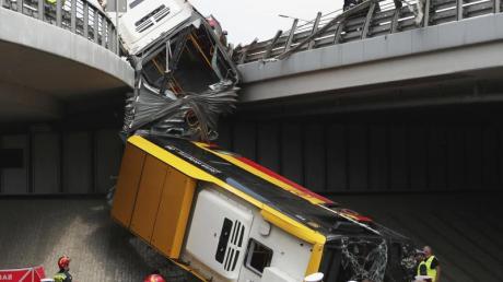 Einsatzkräfte arbeiten an der Unfallstelle. Mindestens ein Mensch ist bei dem Absturz des Linienbusses ums Leben gekommen.