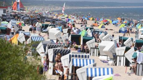 Touristen strömen bei hochsommerlichem Wetter an den Strand auf der Insel Usedom.