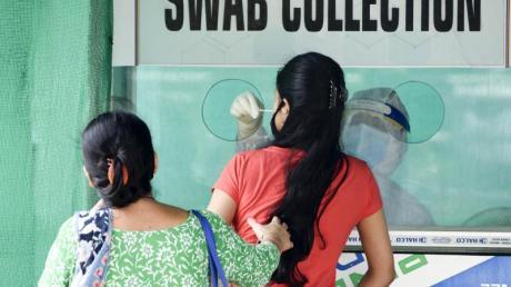 Von einer Frau im indischen Guwahati wird ein Nasenabstrich an einer Entnahmestelle genommen.