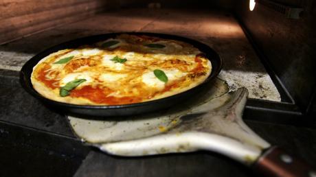 """Die typische Pizza Margherita ist belegtmit Tomaten, Mozarella und Basilikum. Neapel gilt als Welthauptstadt der Pizza und legt Wert darauf, im 18. Jahrhundert die einzig wahre Version, die """"la vera pizza napoletana"""" kreiert zu haben."""
