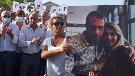 Die Ehefrau des verstorbenen Busfahrers hält während eines Protestmarsches in Bayonne ein Foto von sich und ihrem Mann.