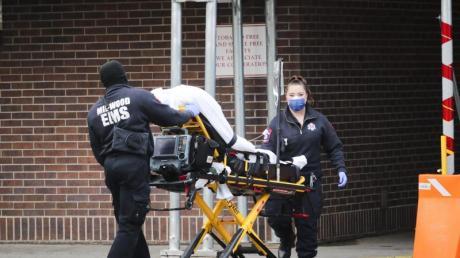 Mitarbeiter des Gesundheitswesens schieben einen Patienten in das Brooklyn Hospital Center in Brooklyn. In der außer Kontrolle geratenen Corona-Pandemie in den USA könnten in den kommenden Monaten nach Modellrechnungen weitere Zehntausende Menschen sterben.