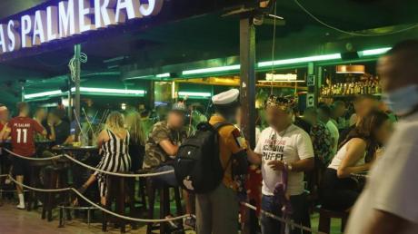 """Touristen halten sich in der Bar """"Las Palmeras"""" in der Bierstraße in el Arenal in Palma de Mallorca auf."""