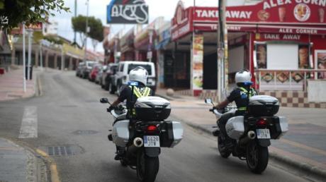 Polizisten überwachen die Lokalsperrungen auf einer Straße in der Touristenhochburg Magaluf.