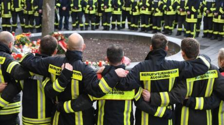 Mitglieder der Berufsfeuerwehr trauern nach der Gewalttat am Königsplatz in Augsburg.