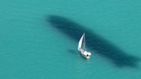Ein Segelboot ist auf dem Bodensee unterwegs, während neben dem Boot der Schatten eines Zeppelin NT im Wasser zu sehen ist.