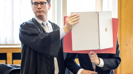 Der Angeklagte, der sein Gesicht neben seinem Anwalt mit einer Mappe verdeckt, wurde nach einem tödlichen Unfall zu einer Bewährungsstrafe verurteilt.
