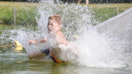 So lässt es sich die Hitze aushalten:Ein Junge rutscht eine Wasserrutsche hinunter.