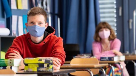 Schüler und Schülerinnen eines Gymnasiums tragen Mundschutze.