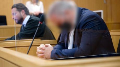 Der Angeklagte sitzt vor Beginn seines Prozesses in einem Saal des Aachener Landgerichts neben seinem Rechtsanwalt.
