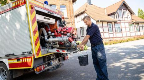 Einsatzkräfte der Freiwilligen Feuerwehr zapfen Löschwasser aus dem Tank eines ihrer Einsatzfahrzeuge.