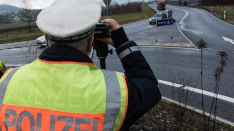 Ein Polizist misst die Geschwindigkeit passierender Autos. Die neuen Rgelungen des Bußgeldkatalogs für Verkehrssünder sind wegen eines Formfehlers zurzeit in Teilen außer Vollzug gesetzt.