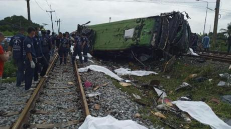Rettungskräfte stehen an einem beschädigten Zug und neben mit weißen Tüchern bedeckten Leichen. Mindestens 17 Menschen sind am Sonntag in Thailand beim Zusammenstoß eines Busses mit einem Zug ums Leben gekommen.