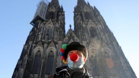 Lorenz steht mit Clownsnase auf der Maske vor dem Kölner Dom.