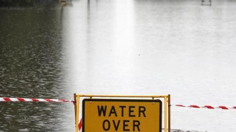 Ein Schild mit Warnhinweis auf einer überfluteten Straße bei Windsor. Tagelanger Starkregen hat im Osten Australiens die schlimmsten Überschwemmungen seit Jahrzehnten ausgelöst.