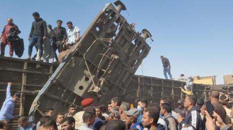 Menschen versammeln sich nach dem Zusammenstoß der Züge an den beschädigten Waggons.