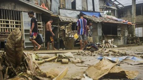 """Anwohner räumen Trümmer von den Überschwemmungen durch den Taifun """"Surigae"""" auf."""