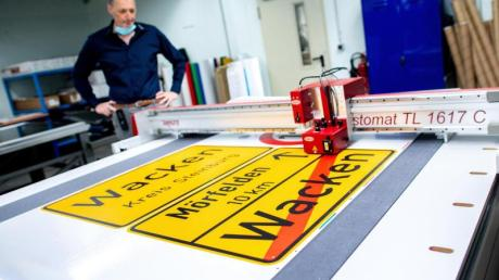 Michael Mazur, Abteilungsleiter Druckverfahren in der Fritz Lange GmbH, begutachtet den Zuschnitt einer Ortstafel von Wacken auf spezieller selbstklebender Folie.