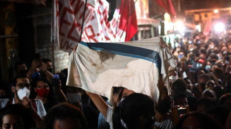 Proteste am Tag nach dem tödlichen Polizeieinsatz: Eine Frau zeigt eine Schuluniform mit einem Blutfleck.