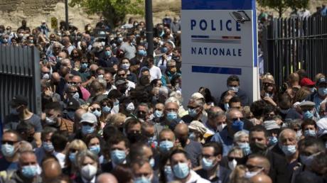 Zahlreiche Polizeibeamte und Zivilisten versammeln sich an einer Polizeistation, um dem getöteten Polizisten zu gedenken.